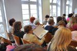 Zbliżenie widowni siedzącej na krzesłach po lewej stronie sali. Na ścianie okna i szklane drzwi. Na widowni siedzą tylko kobiety. Jedna z nich przegląda książkę prezentowaną podczas prelekcji. Jest to siedziba WBP w Starym Ratuszu, czytelnia czasopism na parterze.