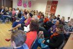 Zdjęcie widowni wykonane z prawej strony sali. Krzesła ustawione z półkole na całej sali, na nich widownia słuchająca przemówienia Agaty Passent. Po prawej na ścianie gobelin, naprzeciwko pod sufitem wiszą plakaty i kartonowe kółka DKK.